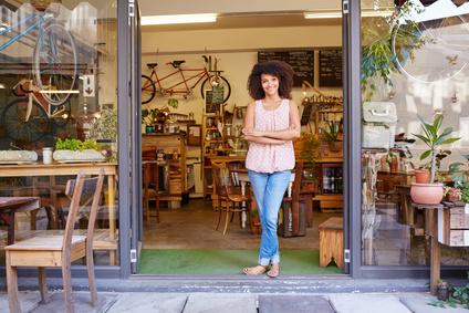Femme d'entreprise souriante à la porte de sa boutique